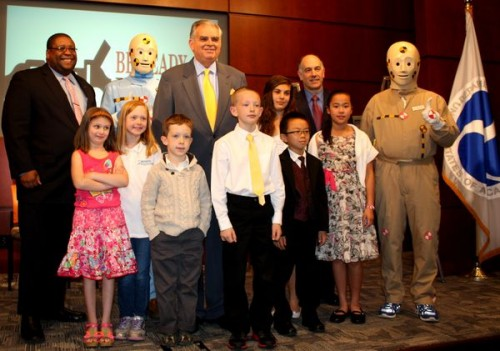 "National Highway Traffic Safety Administrator David Strickland, on the left, U.S. Secretary of Transportation Ray LaHood, i the middle, and Federal Motor Carrier Safety Administration (FMCSA) Deputy Administrator Bill Bronrott (to the right of Secretary LaHood) and two crash test dummies pose for a photo with the 10 2013 winners of the ""Be Ready. Be Buckled."" Safety Belt Student Art Contest."