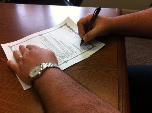 man signs legal document