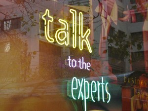 "neon sign says ""talk to the experts"""