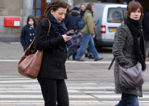 woman texting while crossing street