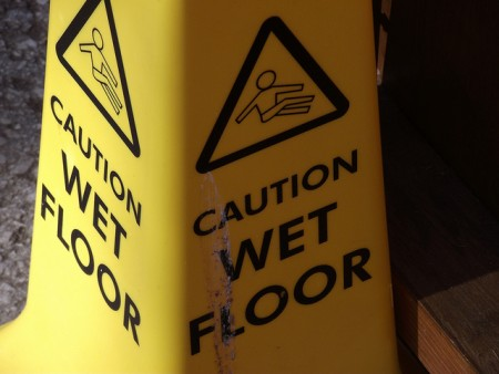yellow safety cone reads 'caution wet floor'