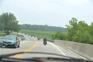 Motorcyclists ride single file down a two-lane street.