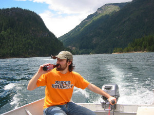 A man drinks a beer while operating a motorboat.