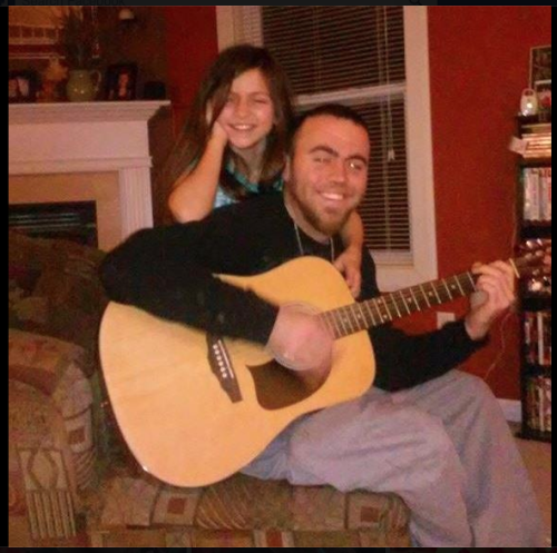 Sam Haynes, playing a guitar, poses for photo with little girl.